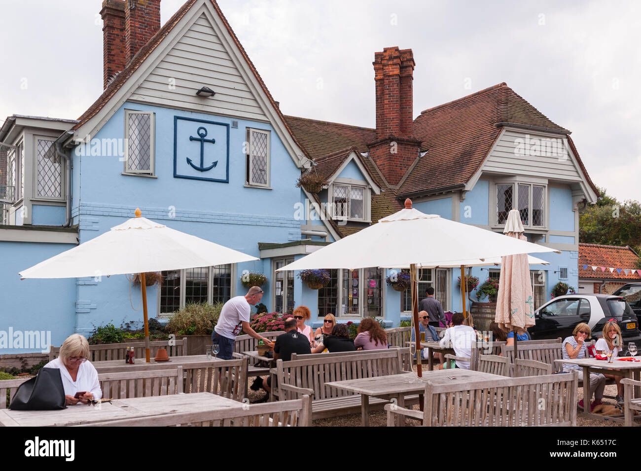 Customers sitting outside The Anchor pub in Walberswick , Suffolk , England , Britain , Uk - Stock Image