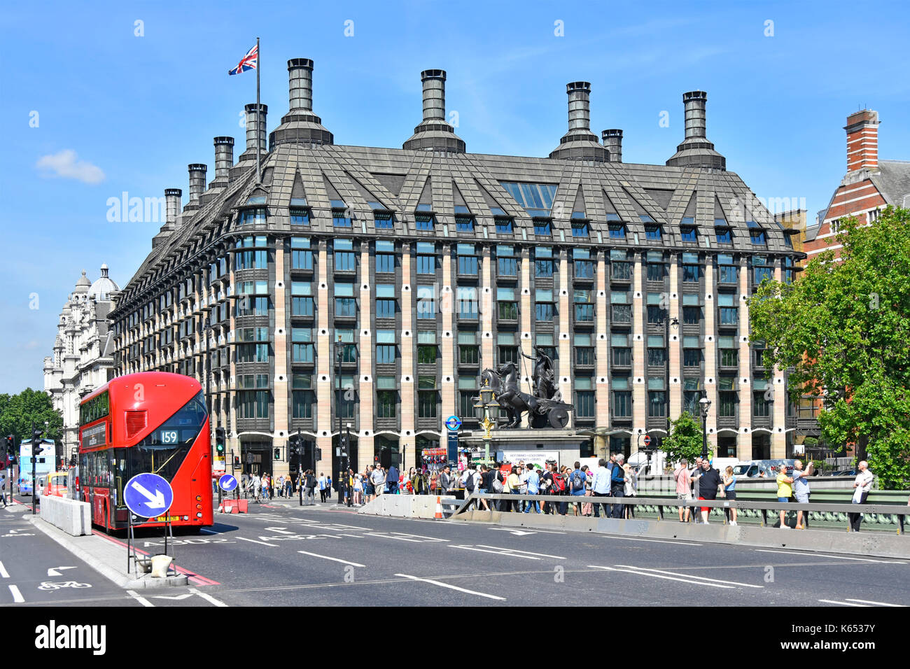 Portcullis House Westminster provides offices for members of parliament and their staff tourists on Westminster Bridge new temporary security barriers - Stock Image