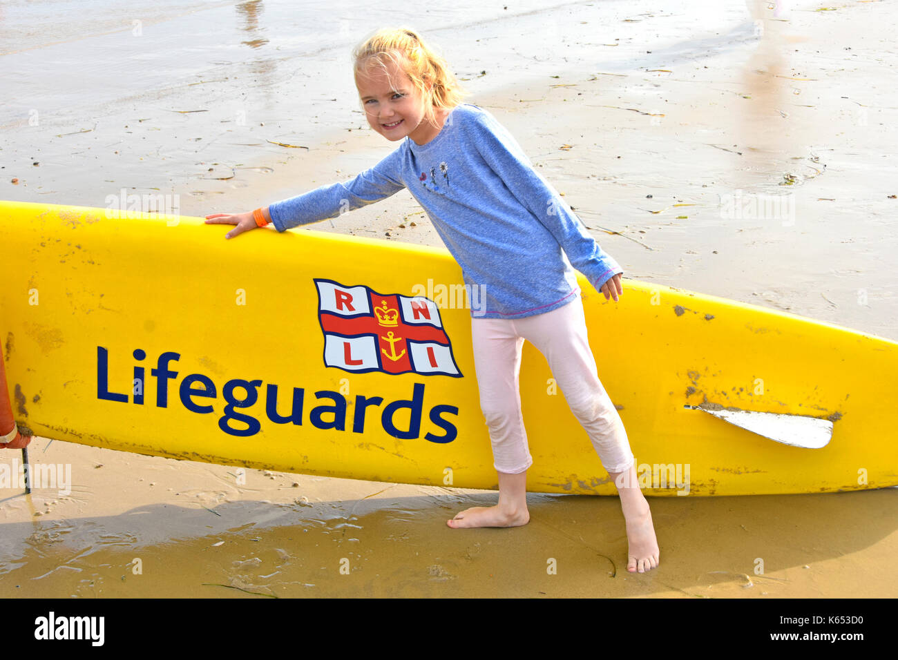 Six year old girl posing at seaside beside a RNLI Lifeguards surfboard awareness idea of sea bathing hazards chilly summer holiday to Dorset beach UK - Stock Image