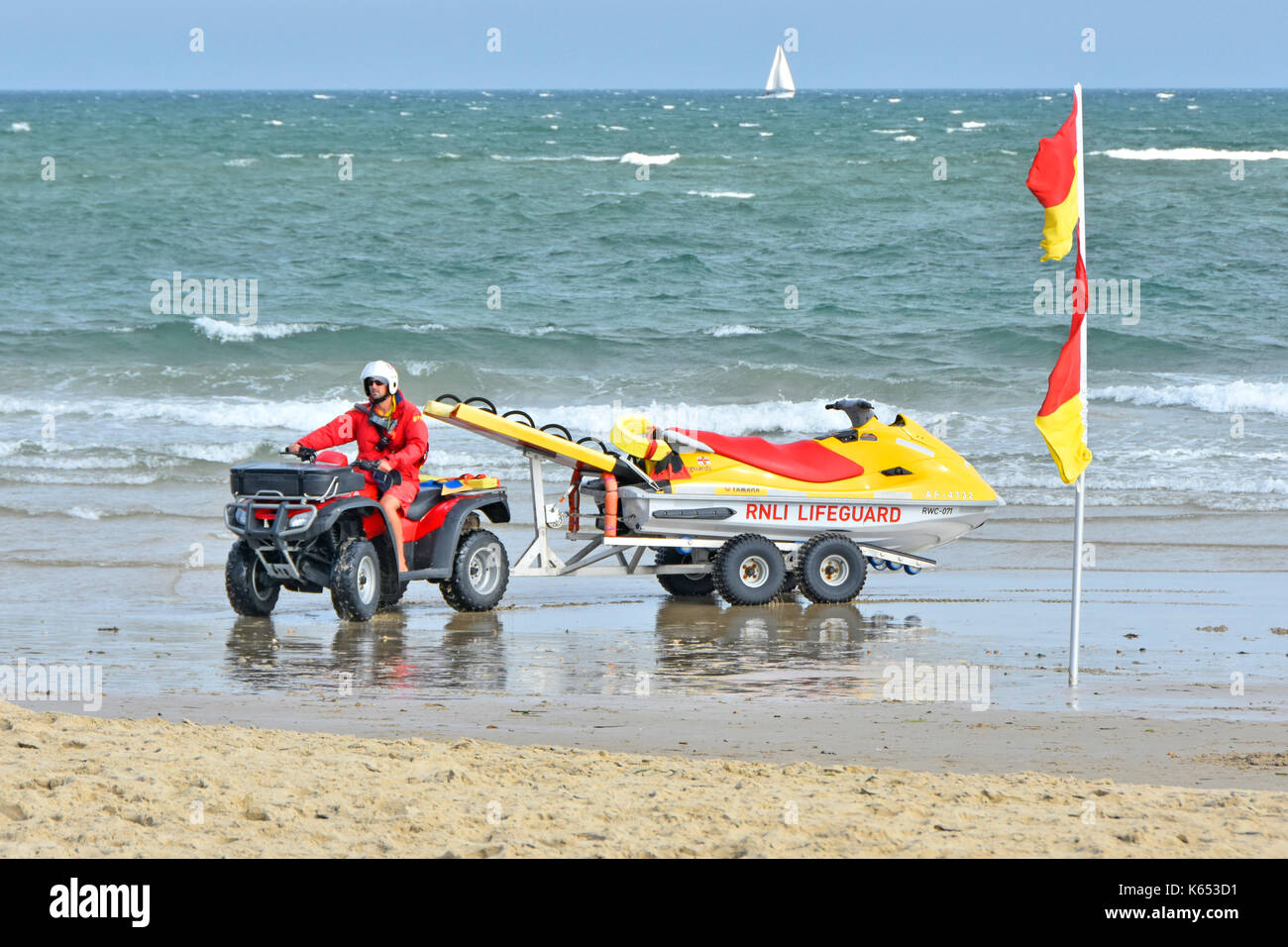 RNLI Lifeguard on the shoreline at Sandbanks beach driving a ATV quad bike and Yamaha jet ski PWC rescue craft with choppy sea & sailing boat distant - Stock Image