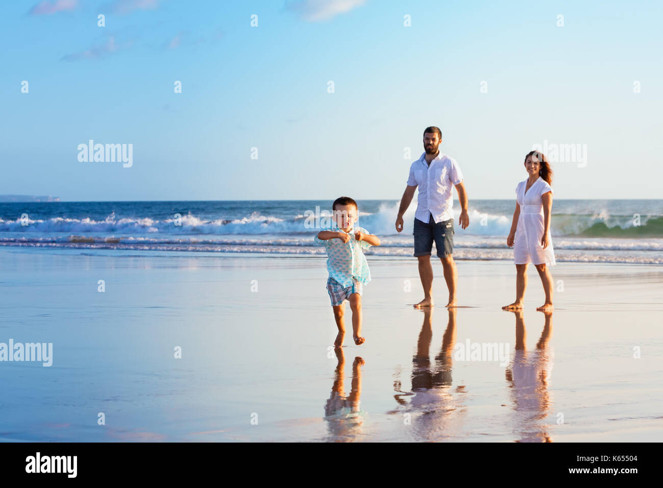 Happy family - father, mother, baby son have fun together, child run with splashes by water pool along sunset sea surf on black sand beach. Travel lif - Stock Image