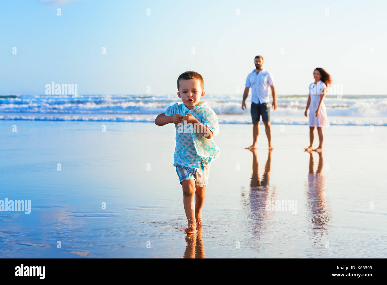 Happy family travel - father, mother, baby son have fun together, child run with splashes by water pool along sunset sea surf on black sand beach. - Stock Image