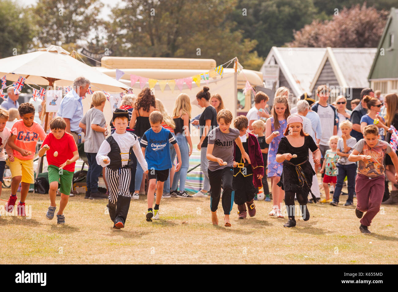 Children running an egg and spoon race at the village fete in Walberswick , Suffolk , England , Britain , Uk - Stock Image