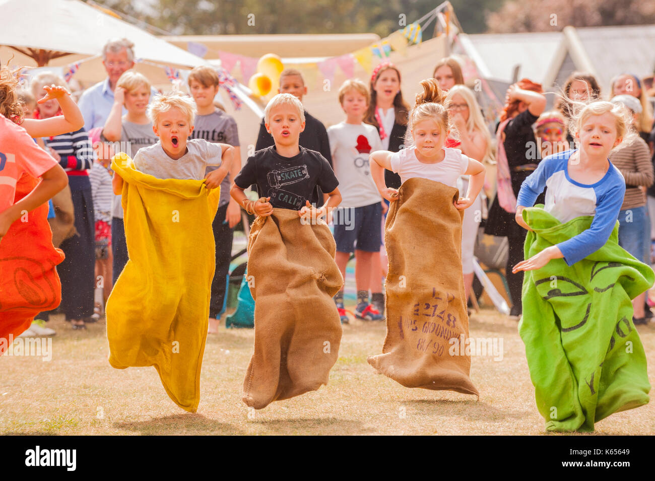 Children running the sack race at the village fete in Walberswick , Suffolk , England , Britain , Uk - Stock Image