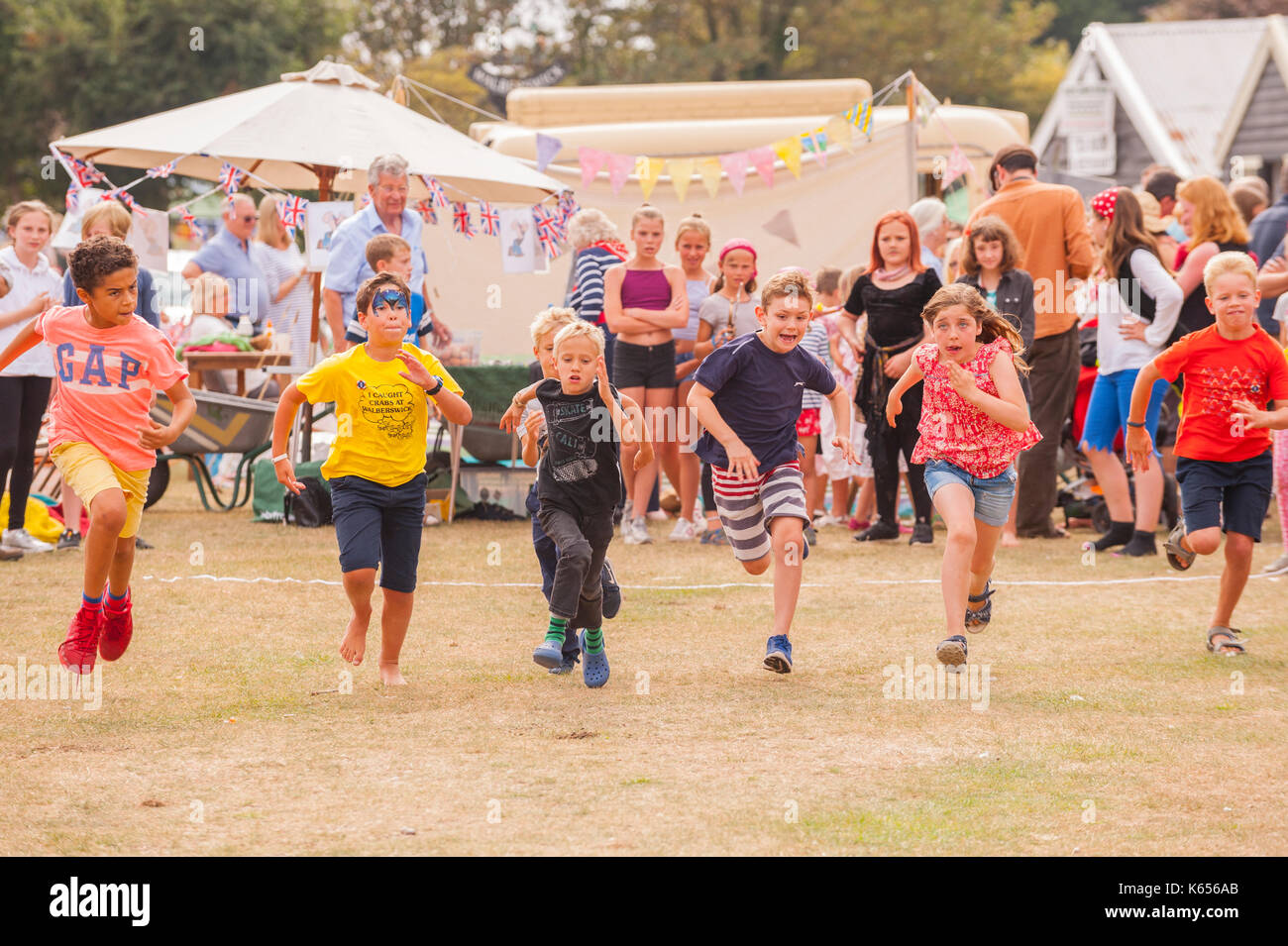 Children running a race at the village fete in Walberswick , Suffolk , England , Britain , Uk - Stock Image