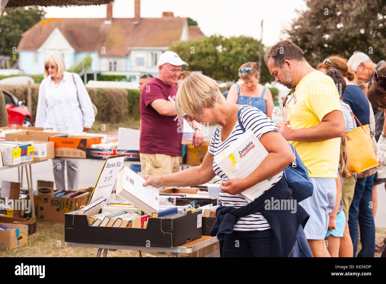 People buying second hand books at the village fete in Walberswick , Suffolk , England , Britain , Uk - Stock Image
