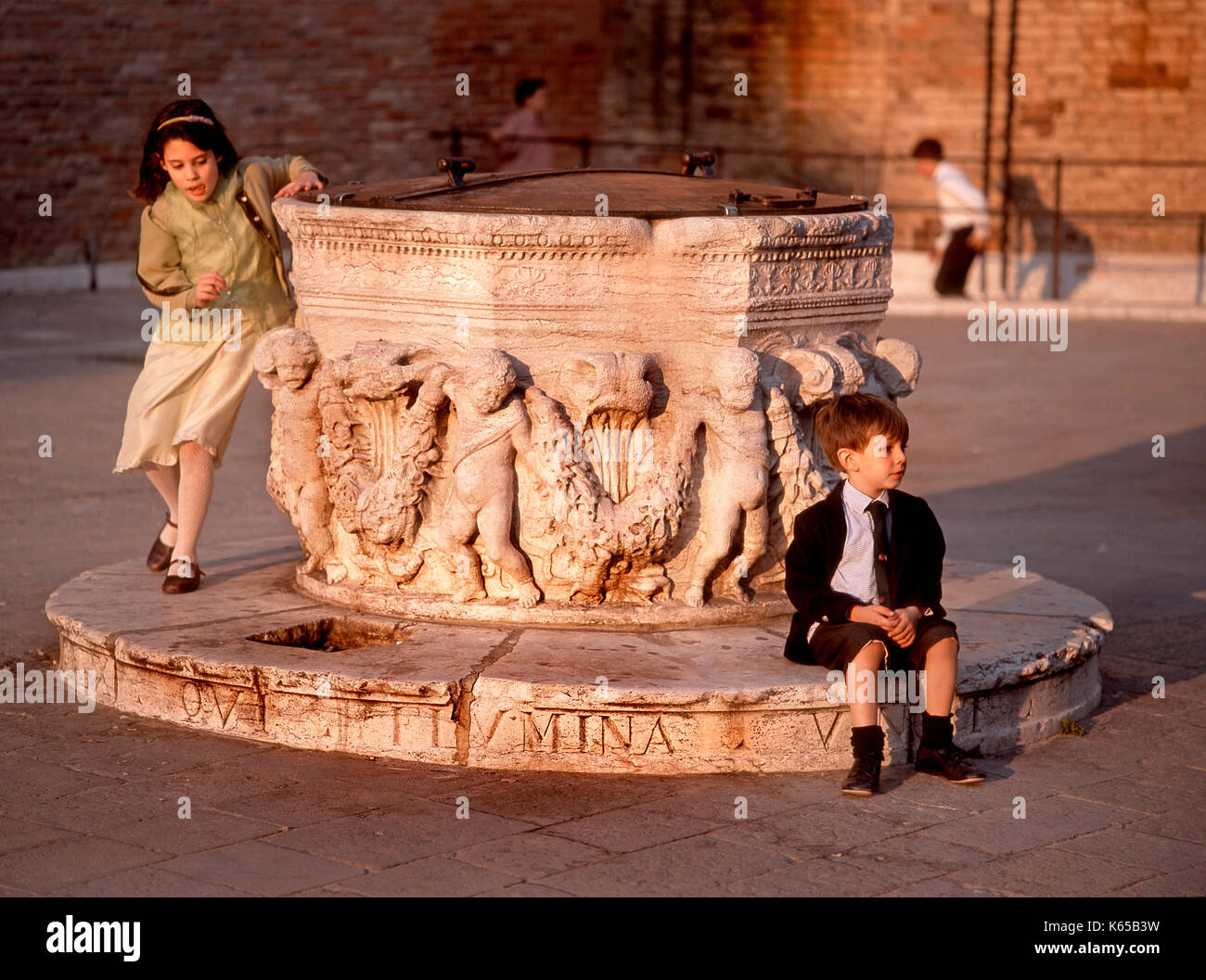 Venice, Veneto, Italy. Children playing around well head in Campo dei Frari - Stock Image