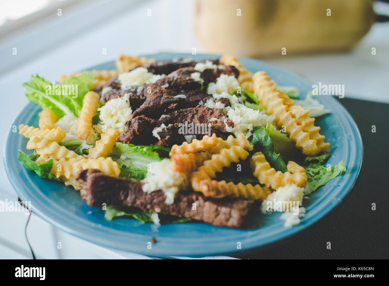 A plate of a steak salad with french fries or chips. Stock Photo