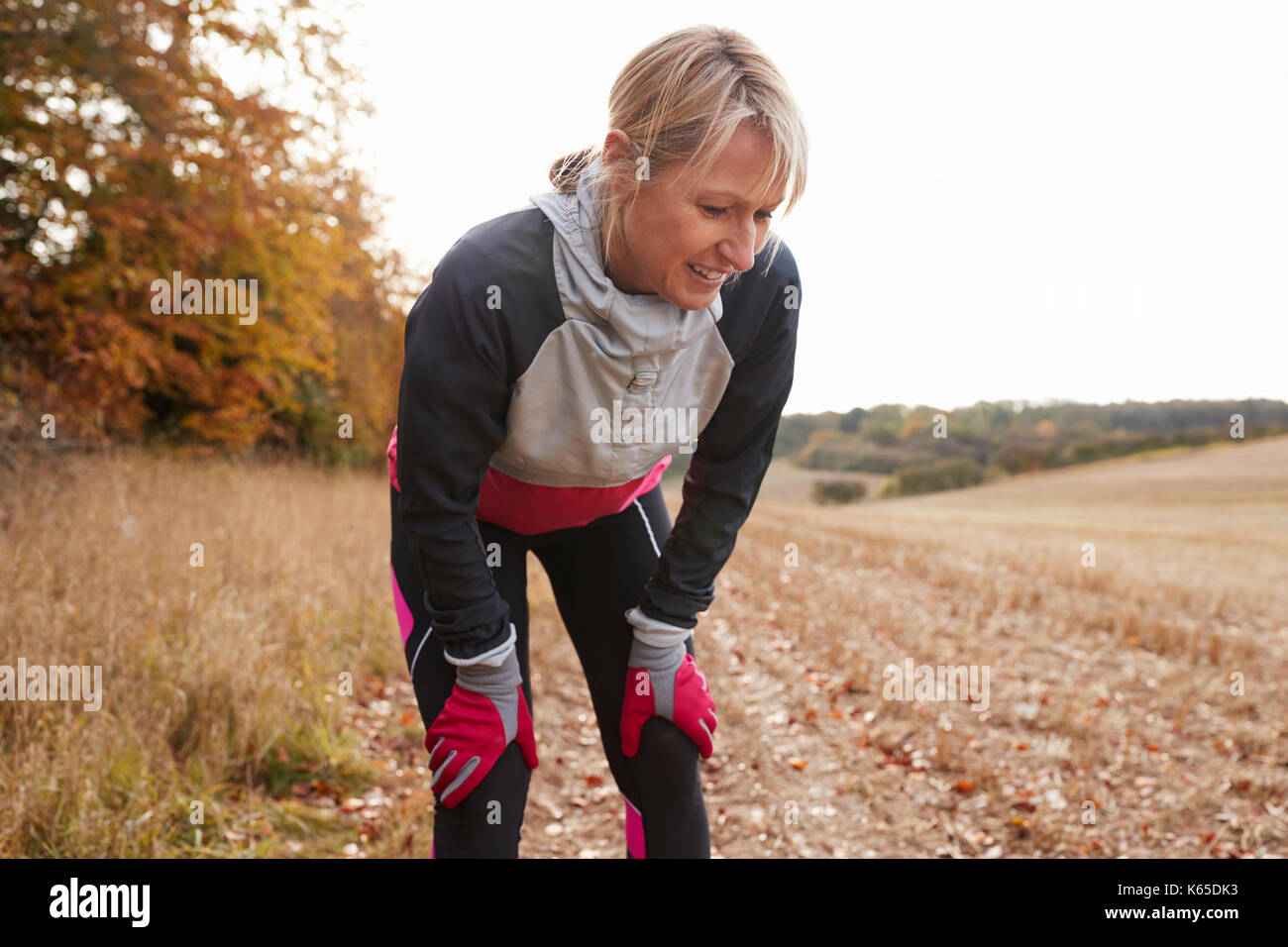 Mature Female Runner Pausing For Breath During Exercise In Woods - Stock Image