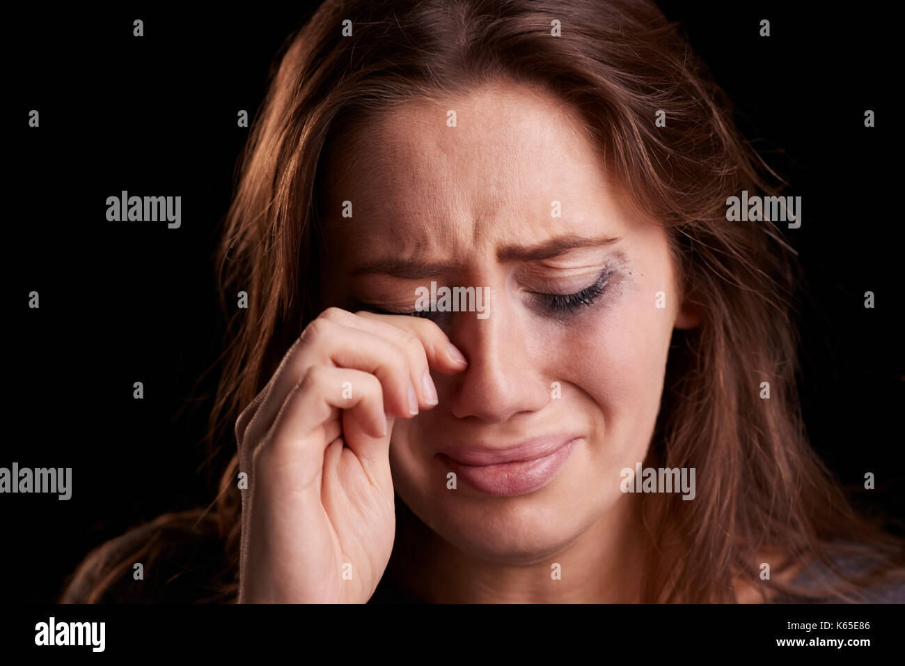 Studio Shot Of Crying Young Woman With Smudged Eye Make Up - Stock Image