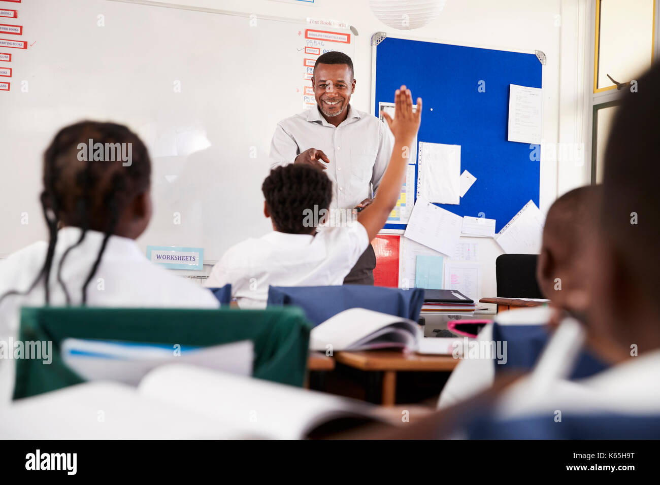 One child raising hand in an elementary school lesson - Stock Image