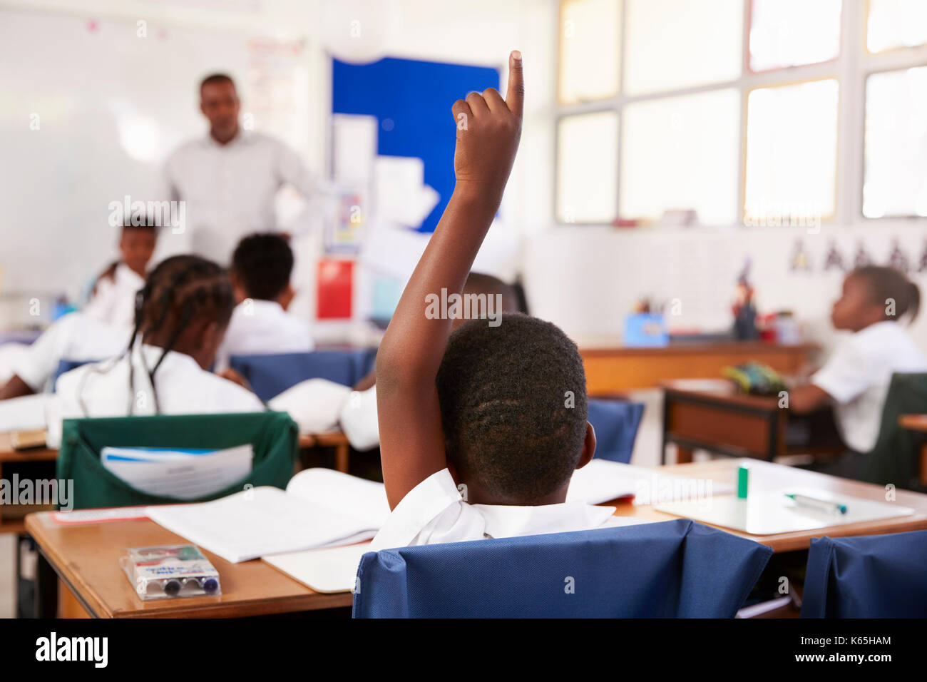 Child raising hand to answer in an elementary school lesson - Stock Image
