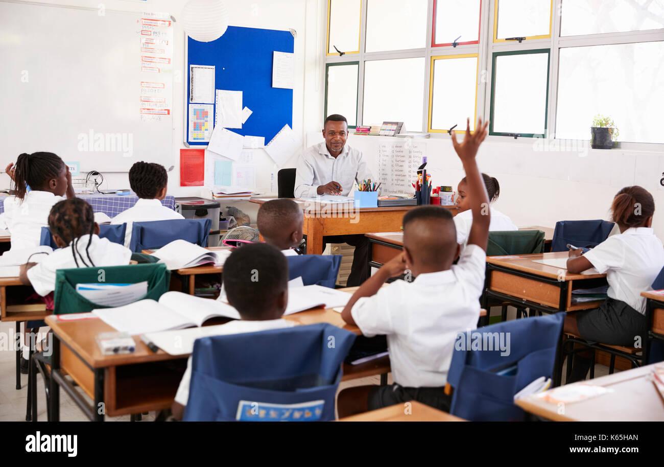 Child raising hand to teacher in an elementary school class - Stock Image