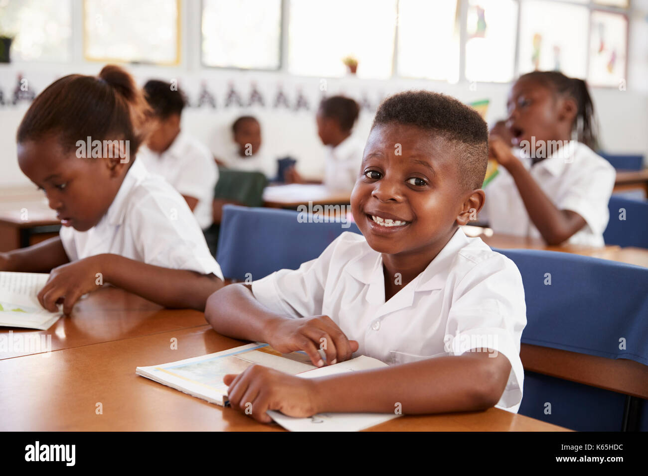 Elementary school boy smiling at camera at his desk in class - Stock Image