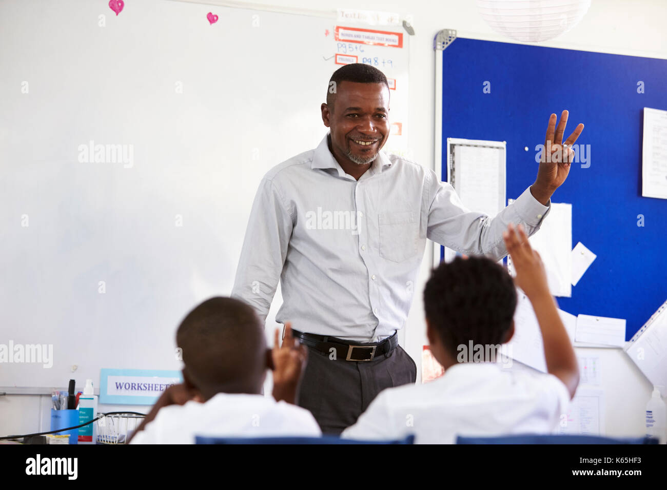 Teacher showing hand in front of an elementary school class - Stock Image