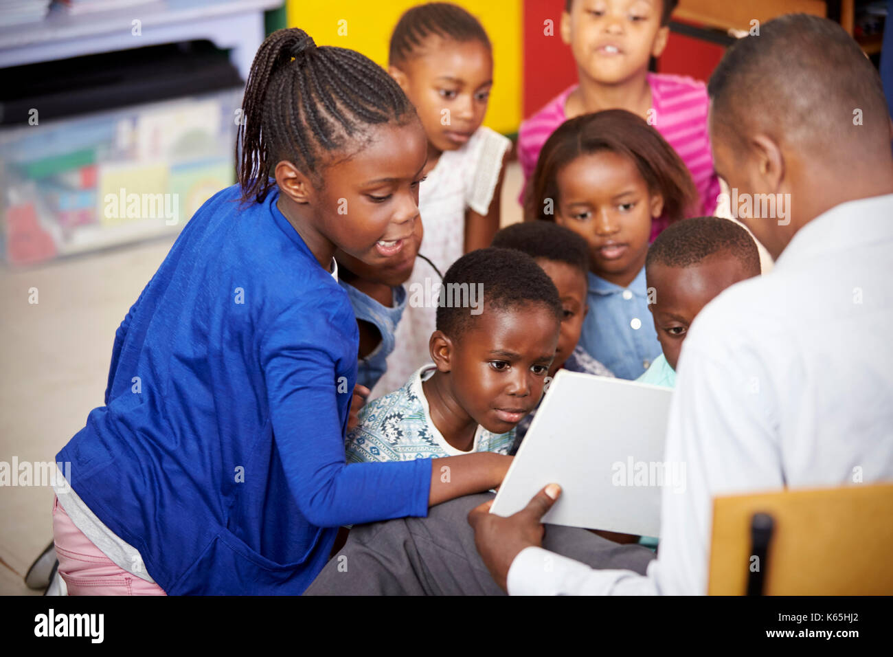 Teacher showing kids a book during elementary school lesson - Stock Image