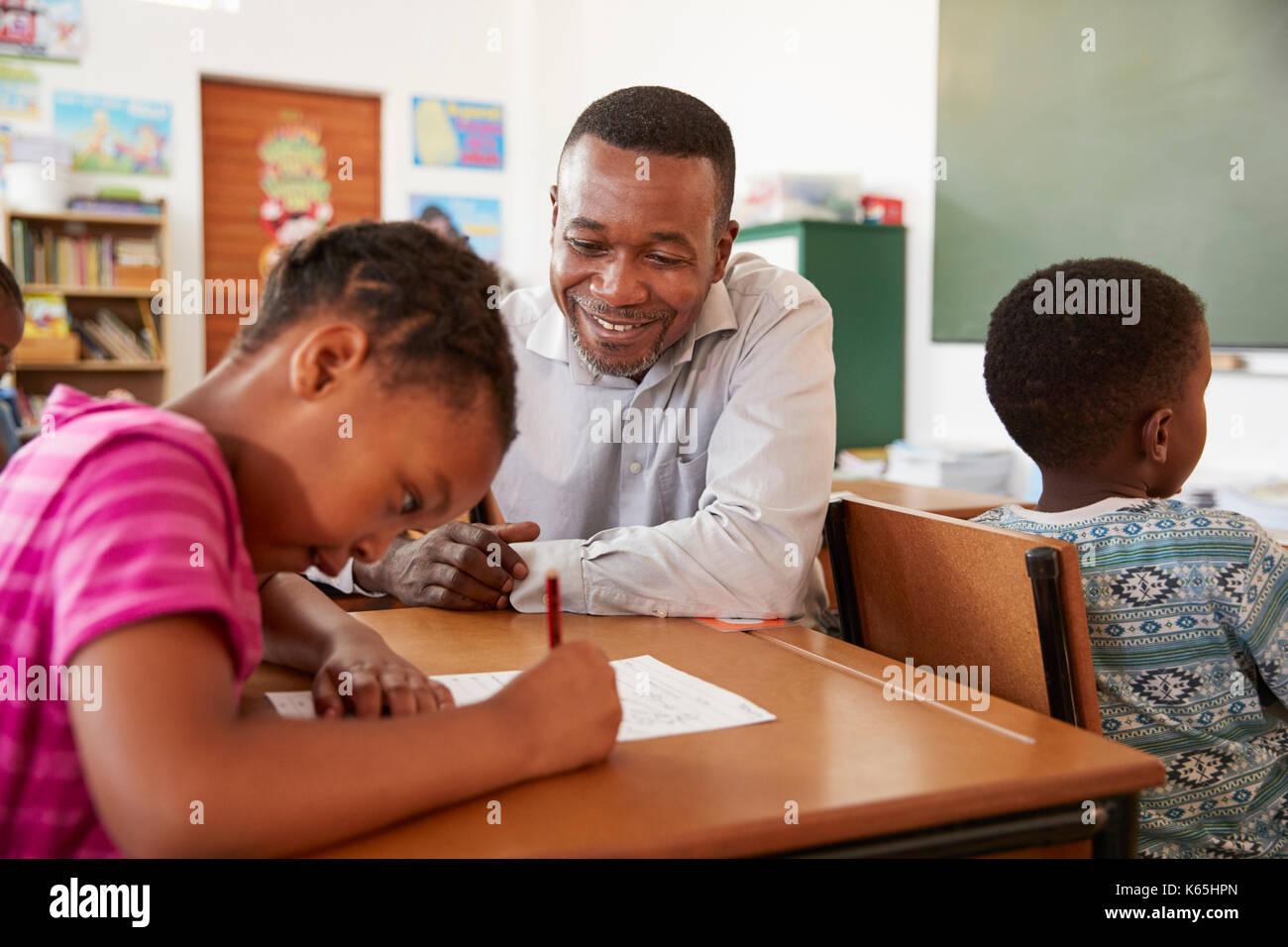 Black male teacher helping elementary school girl in class Stock Photo