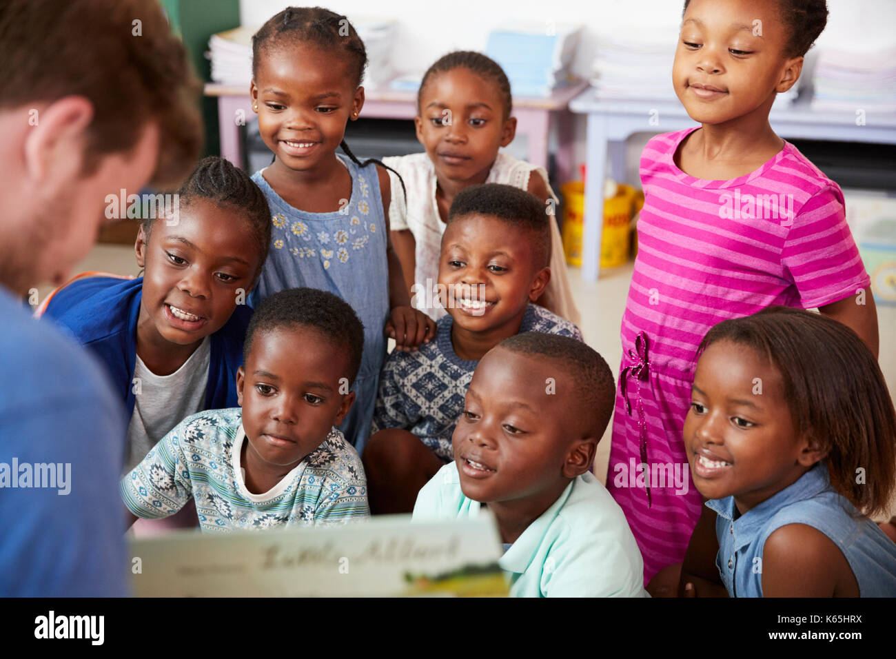 Teacher reading book to elementary school children in class - Stock Image