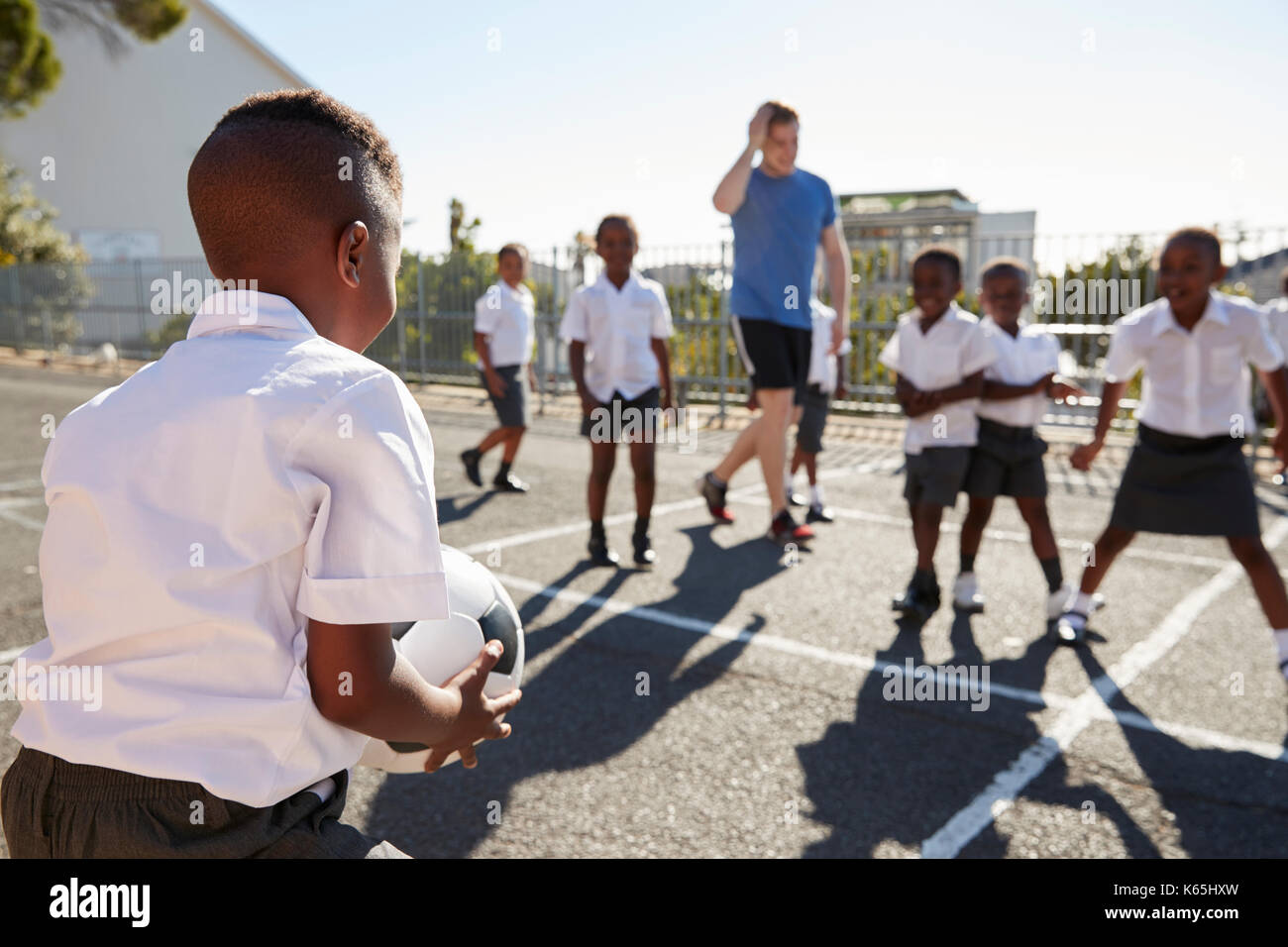 Teacher plays football with young kids in school playground - Stock Image