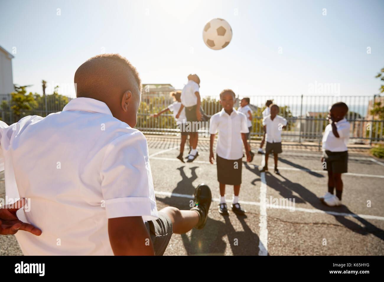 Boy kicking ball to classmates in elementary school playground - Stock Image