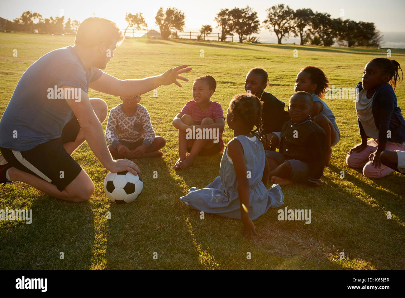 Elementary school kids and teacher sitting with ball in field - Stock Image
