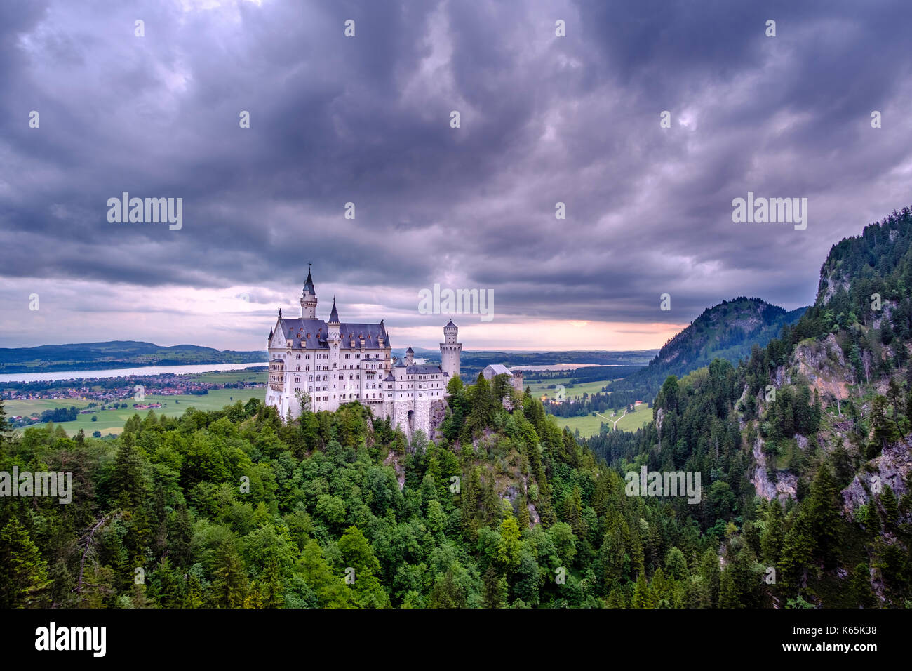 Neuschwanstein Castle at sunrise, seen from the bridge Marienbrücke, built high above the Pöllat Gorge - Stock Image