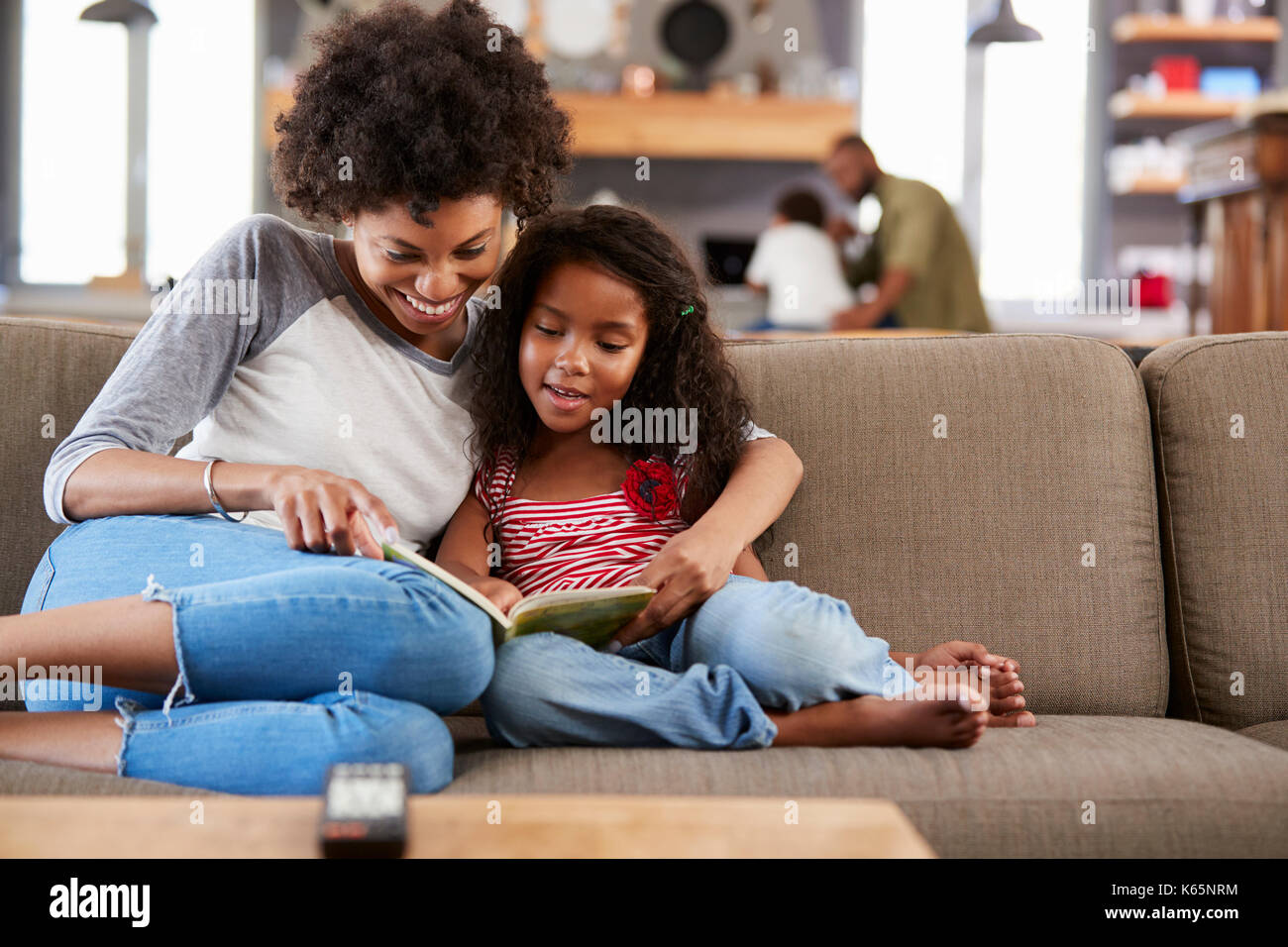 Mother And Daughter Sit On Sofa In Lounge Reading Book Together Stock Photo