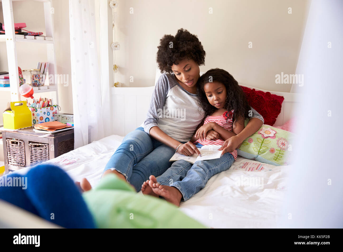 Mother And Daughter Siting On Bed Reading Book Together - Stock Image