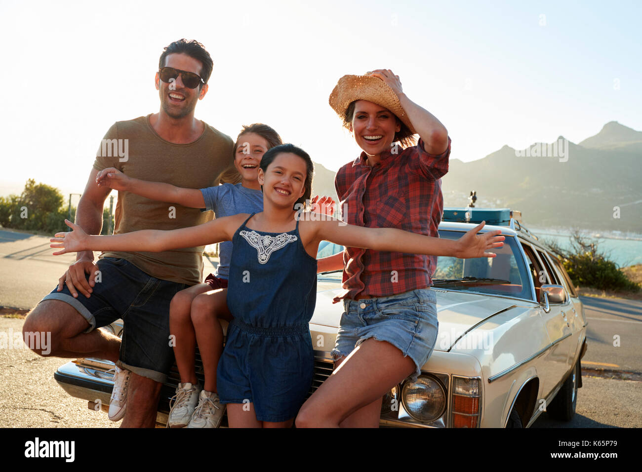Portrait Of Family Standing Next To Classic Car - Stock Image