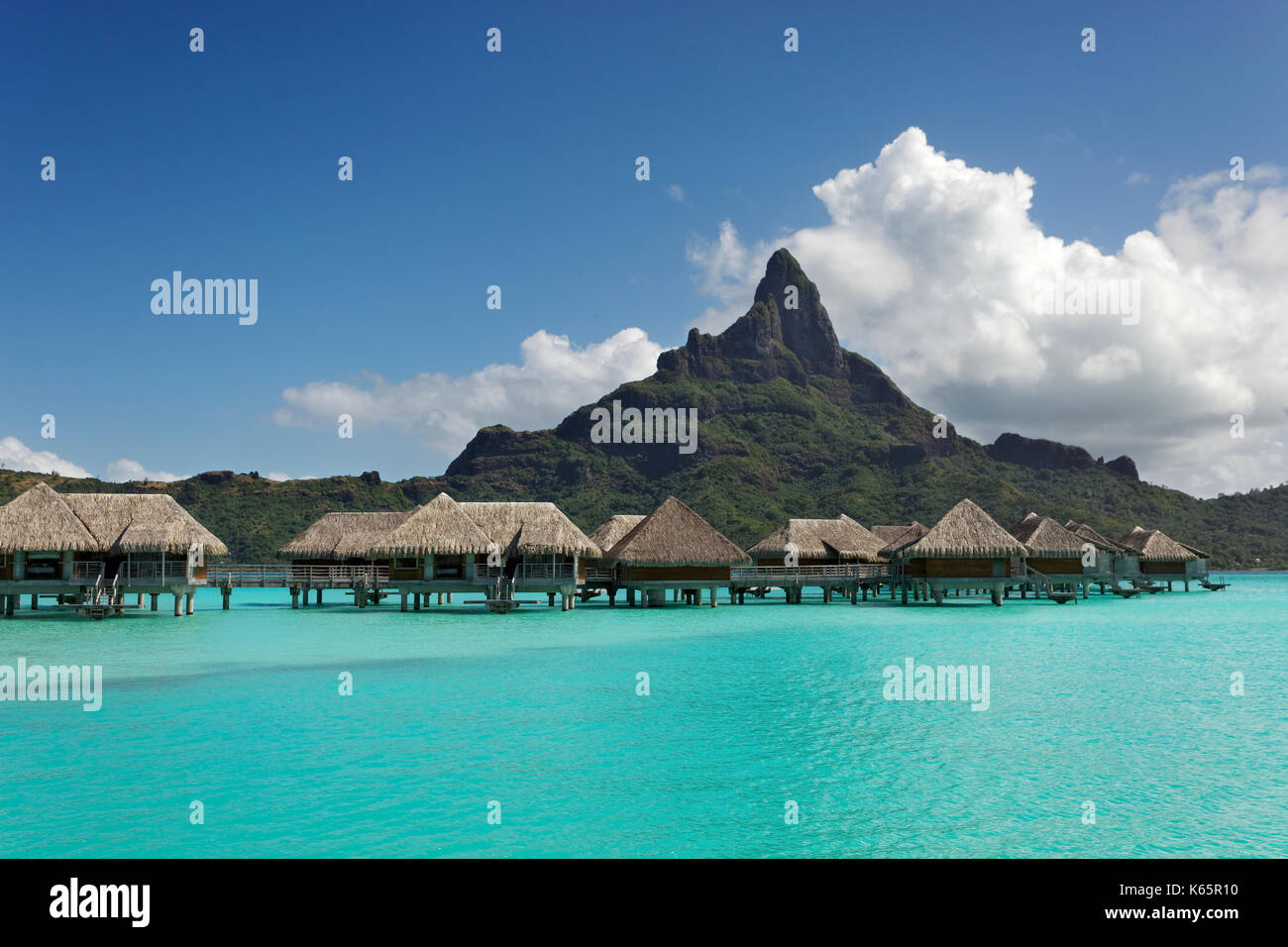 Water bungalows in turquoise lagoon in front of Mont Otemanu, Bora Bora Island, Society Islands, French Polynesia - Stock Image
