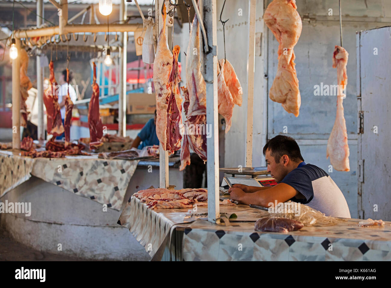 Kyrgyz vendor selling meat at unhygienic butcher stand at food market stall in the city Osh along the Silk Road in Kyrgyzstan - Stock Image