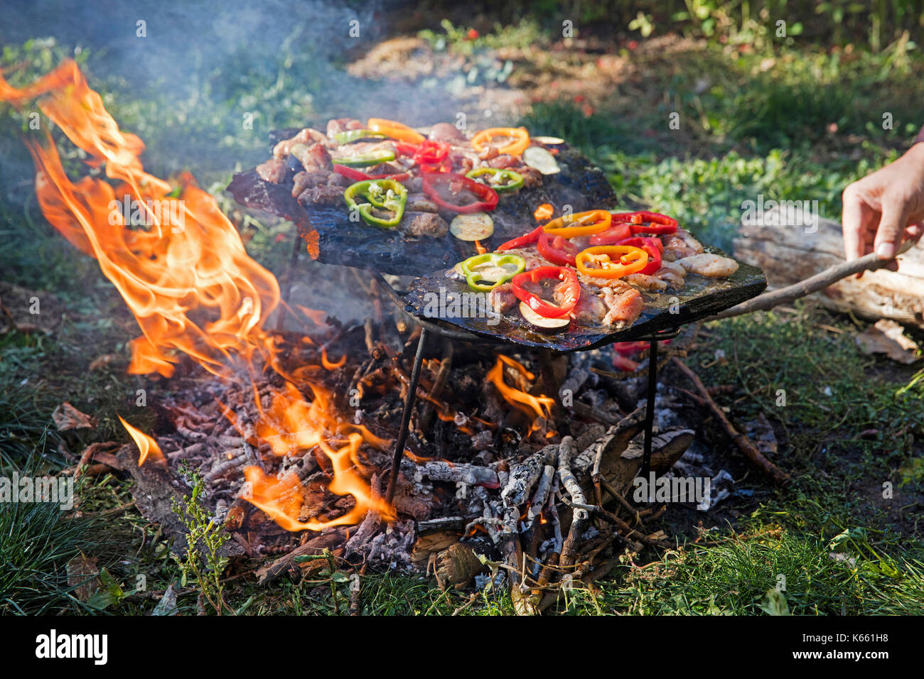 Meat, bell peppers and vegetables cooked on a traditional stone barbecue in Kyrgyzstan - Stock Image
