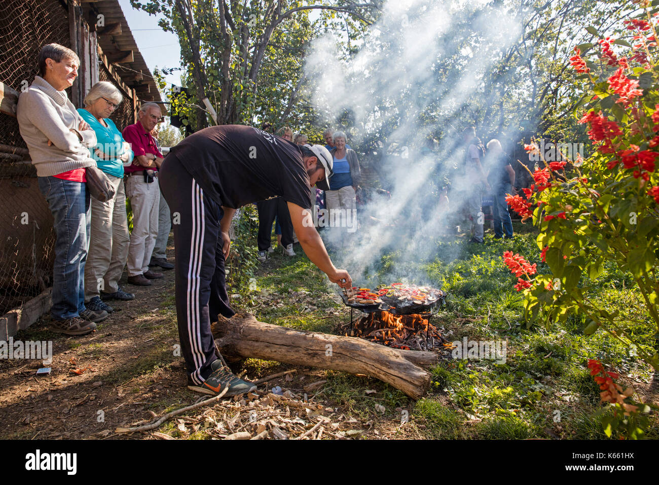 Kyrgyz man cooking food for tourists on a traditional stone barbecue in Kyrgyzstan - Stock Image