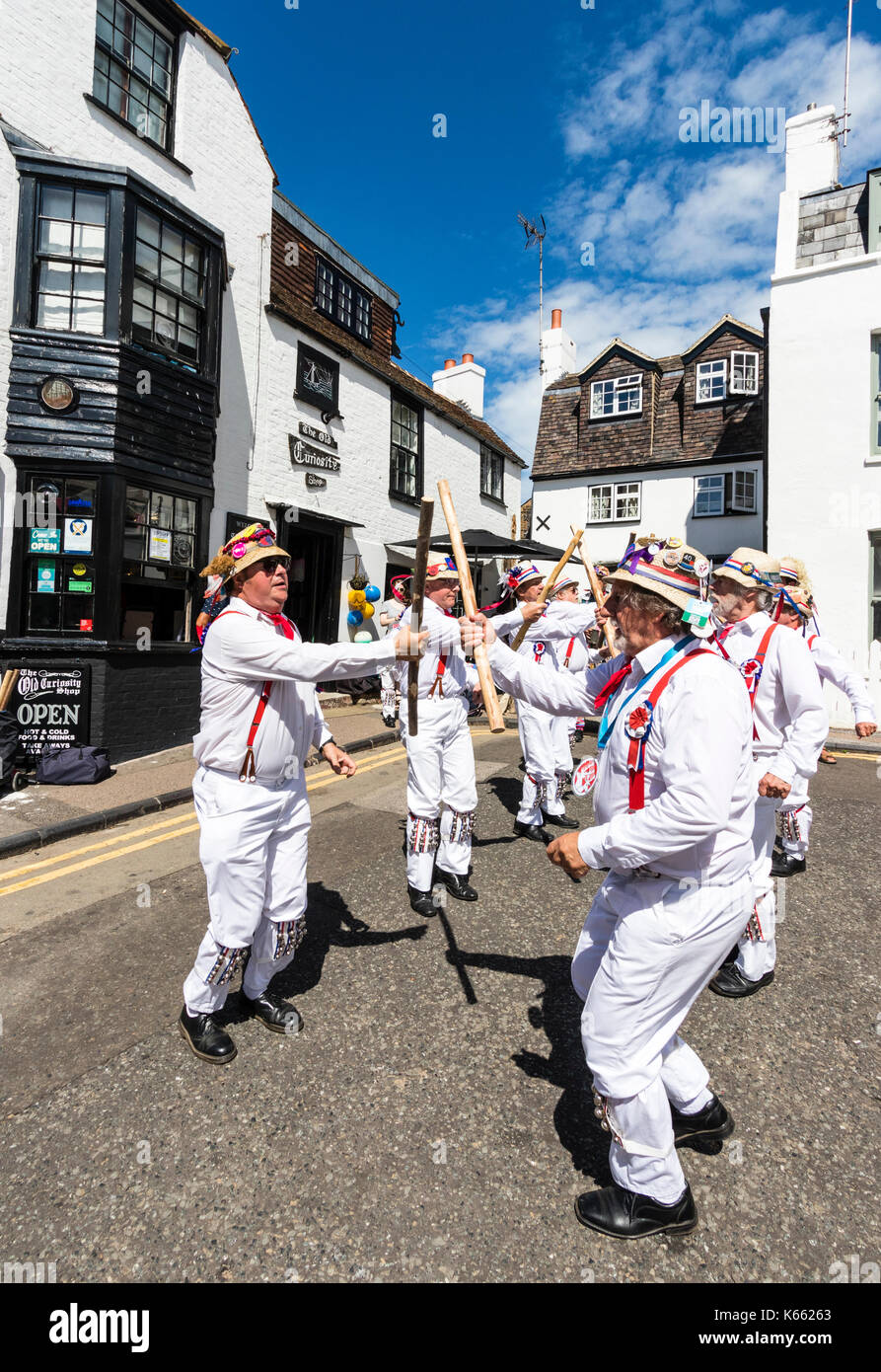 Hartley Morris dancers, in white trousers and shirts, red braces, straw hats, dancing and holding wooden poles by the Old curiosity Shop, Broadstairs. - Stock Image