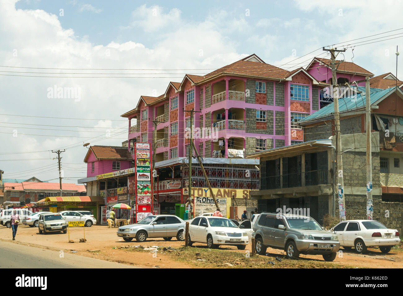 Apartment block with shops and parked vehicles below, Kenya - Stock Image
