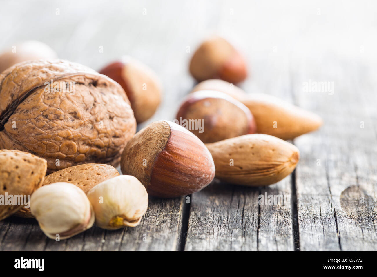 Different types of nuts in the nutshell. Hazelnuts, walnuts, almonds, pecan nuts and pistachio nuts on old wooden table. - Stock Image