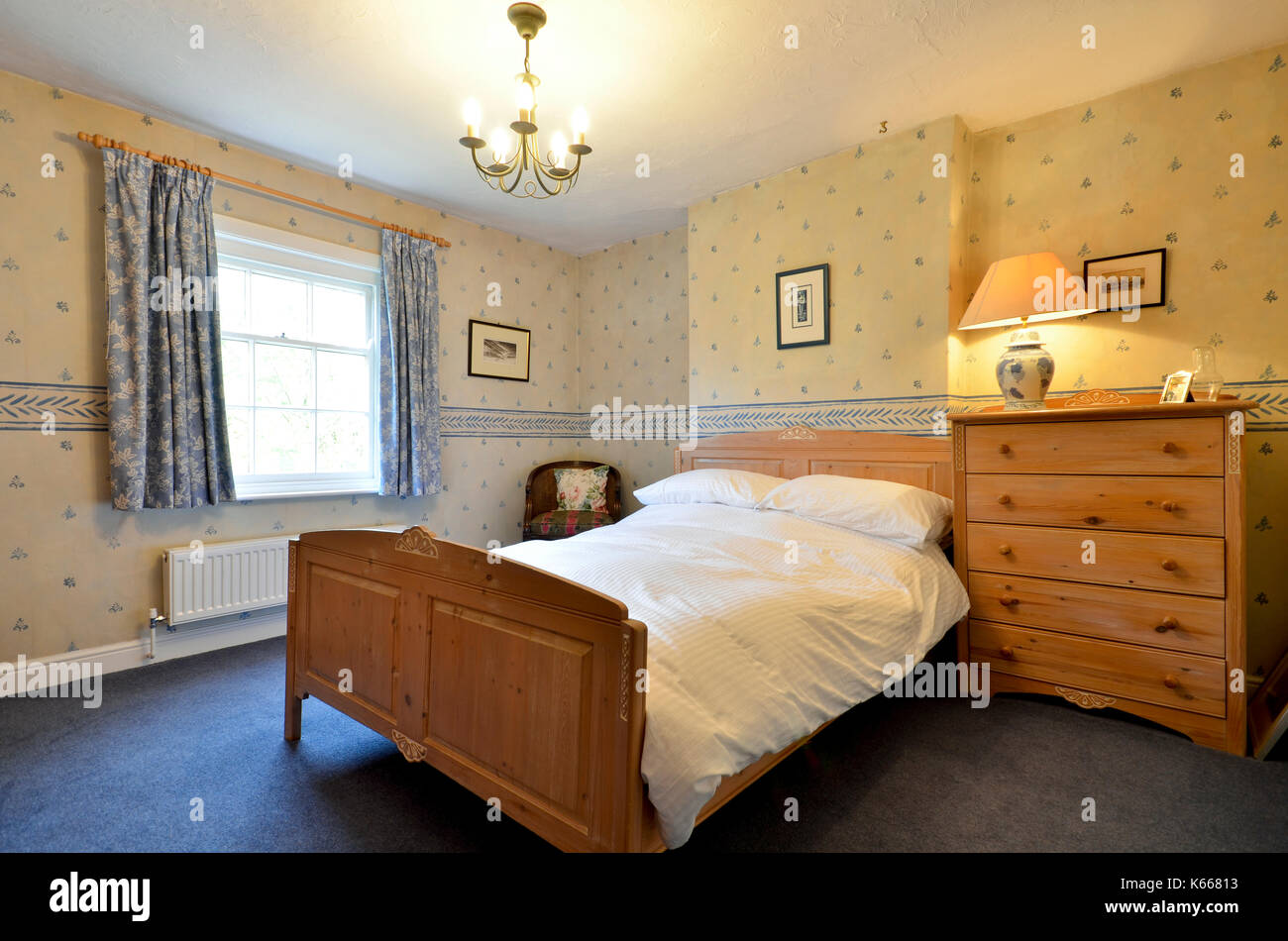 Guest bedroom in country cottage with pine furniture - Stock Image