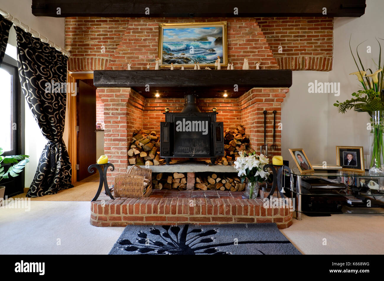 Large brick fireplace with exposed beams and wood burning stove Stock Photo