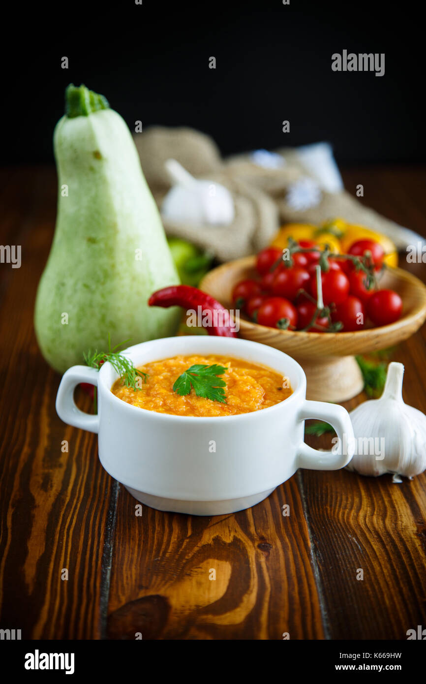 Stewed steamed zucchini with vegetables on a wooden table - Stock Image