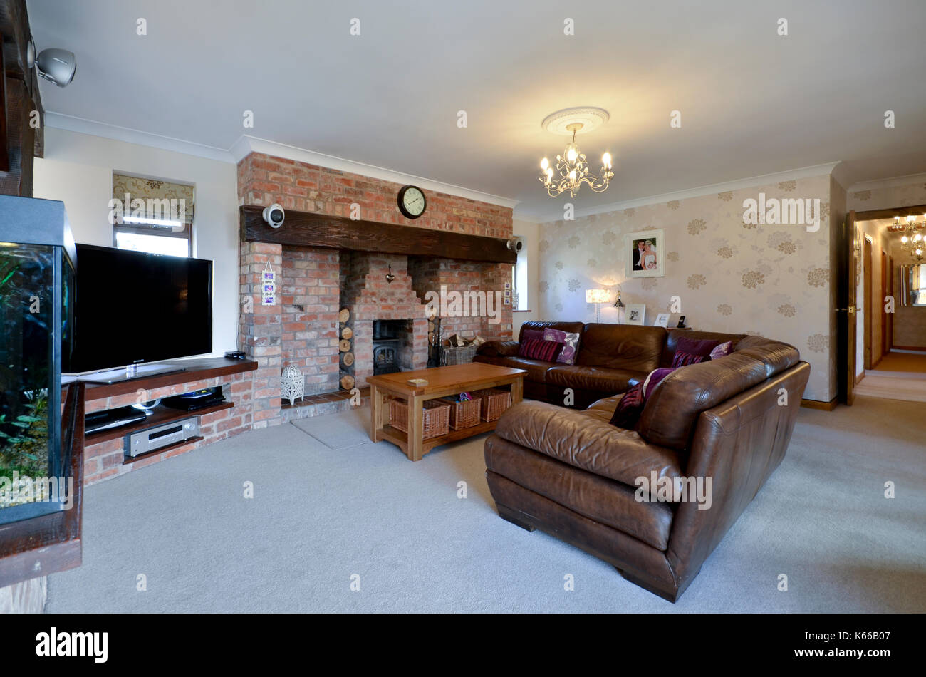 Sitting Room With Large Leather Sofa And Brick Fireplace