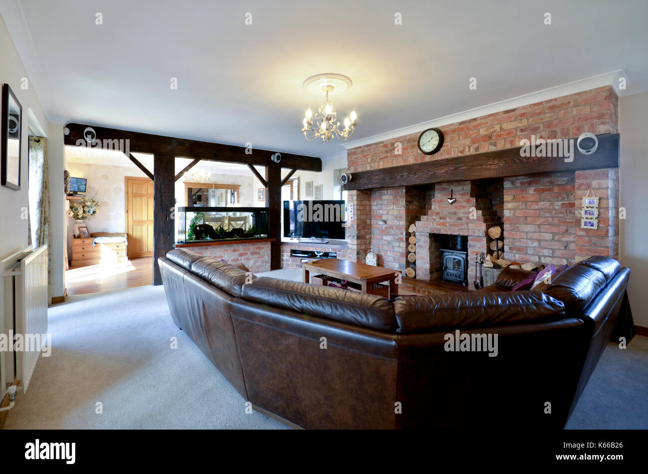 sitting room with exposed beams and large brick fireplace - Stock Image