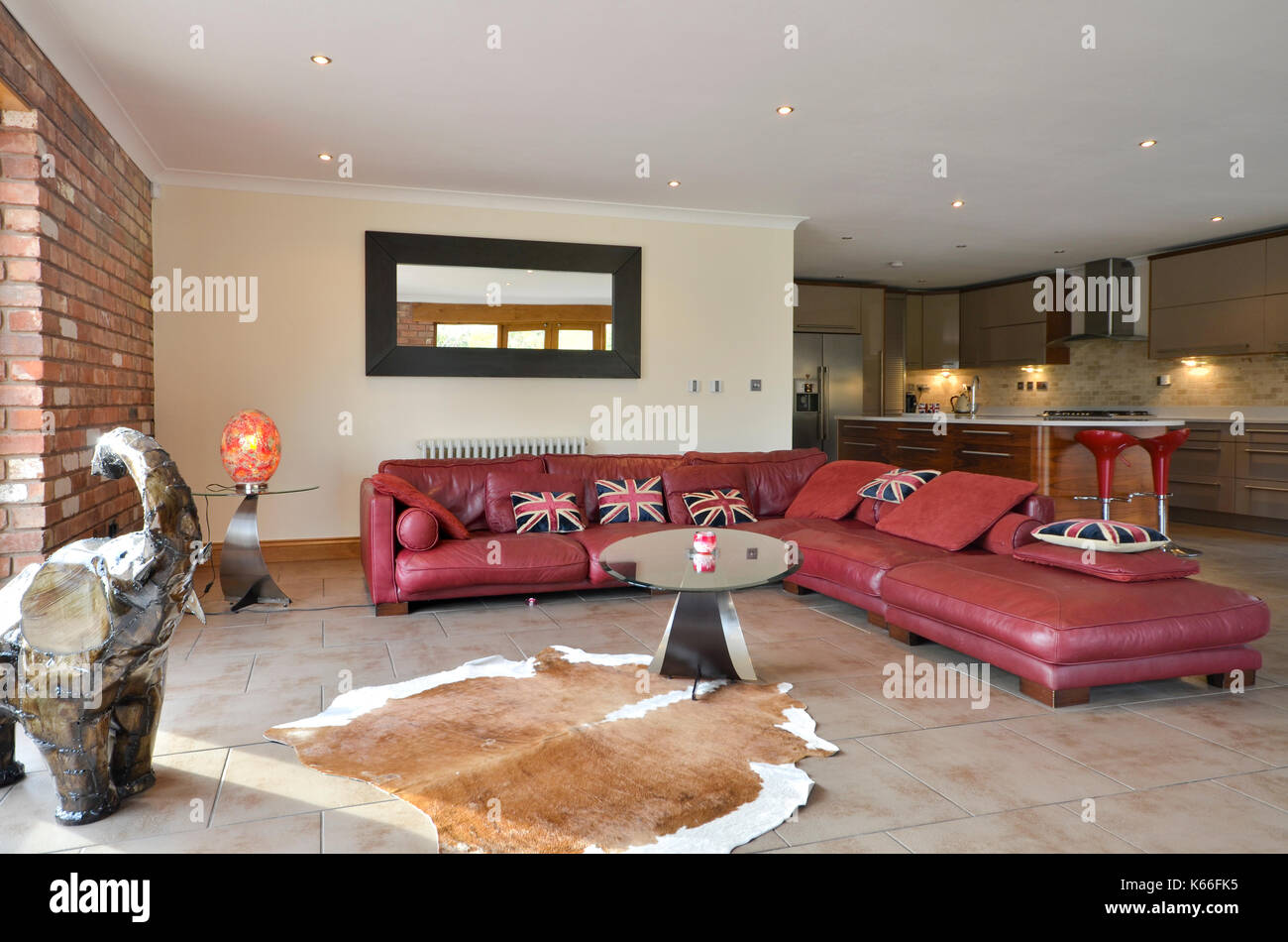 Large red leather corner sofa in open plan kitchen space Stock