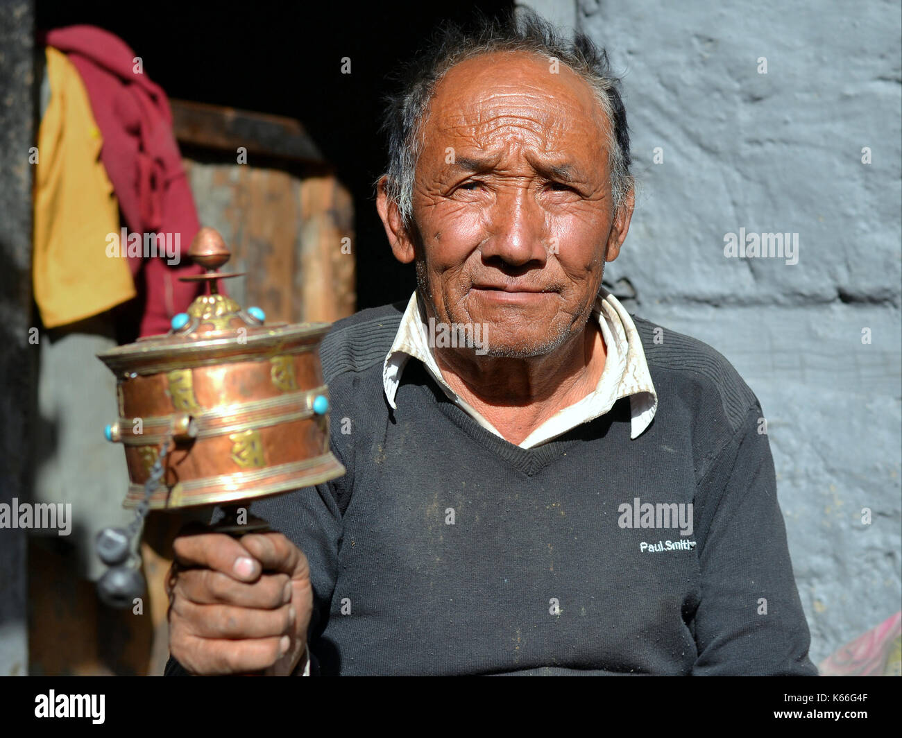 Old Gurung man from Nepal, swinging a Tibetan hand prayer wheel (mani wheel) with his right hand - Stock Image