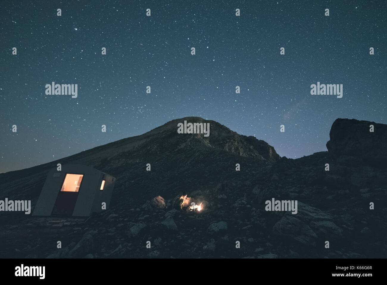 The Milky Way over the mountains, long exposure on the italian-french Alps, mountain hut and refuge illuminated. Toned image, vintage filter, split to - Stock Image