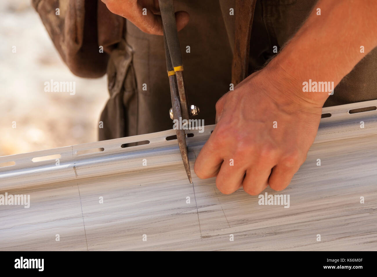 A construction worker cutting through vinyl siding using heavy duty shears in Ontario, Canada. - Stock Image