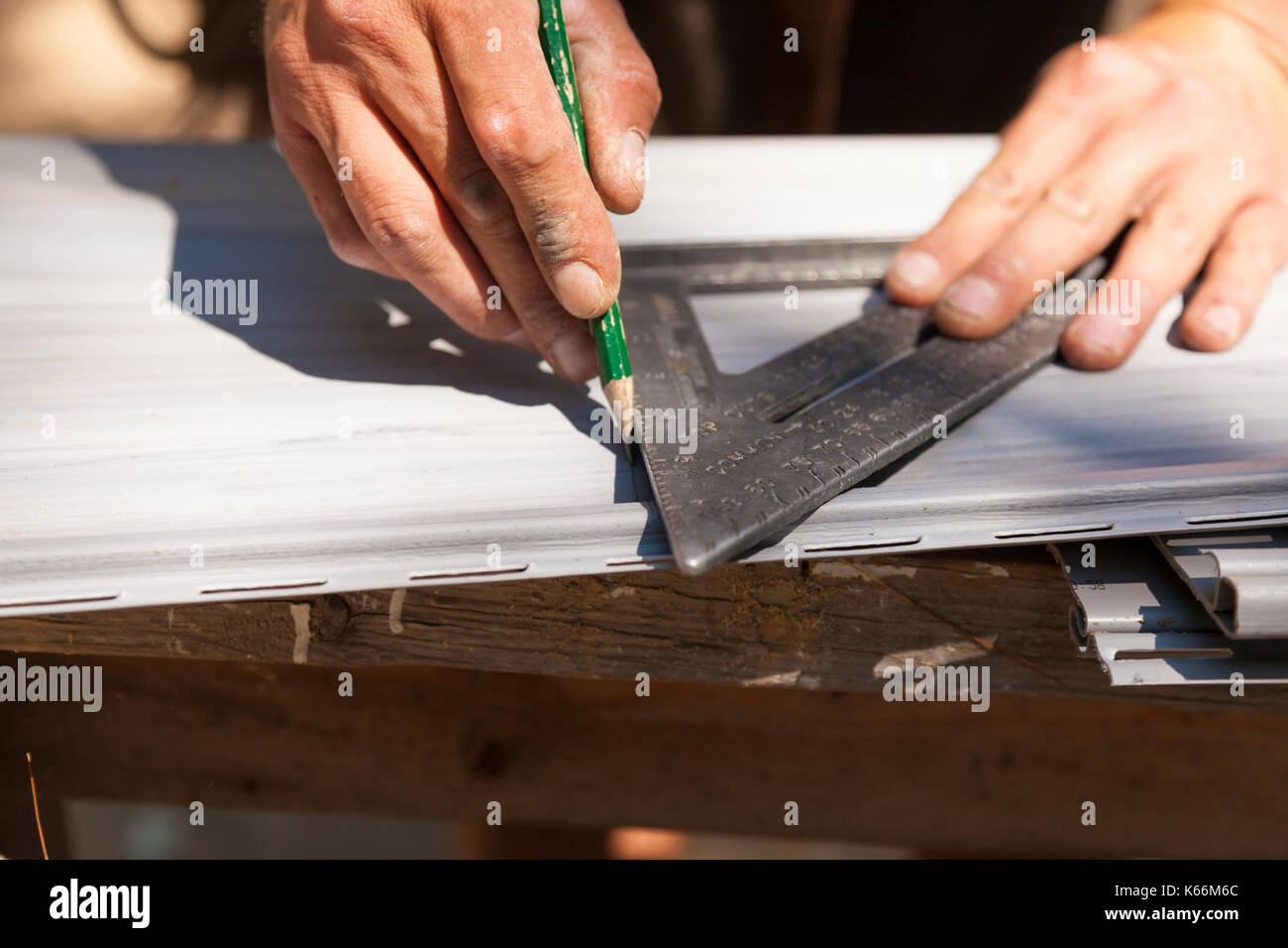 A construction worker marking vinyl siding using a pencil and a triangle or set square in Ontario, Canada. - Stock Image