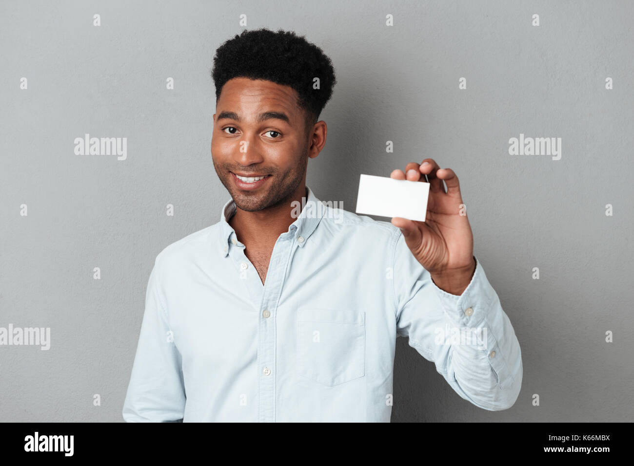 Smiling young afro american guy holding blank business card isolated smiling young afro american guy holding blank business card isolated over gray background colourmoves