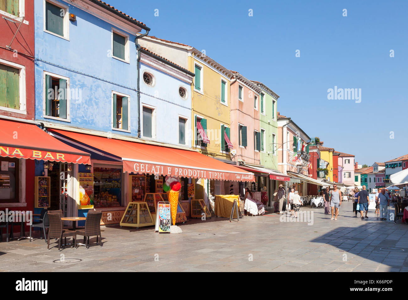 Tourists shopping at colorful stores and restaurants in Via Baldasarre Galuppi, Burano, Venice, Italy, a popular tourist attraction. Burano is known f - Stock Image