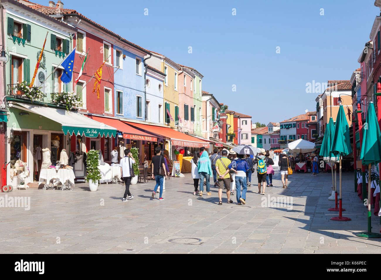 Group of tourists walking through Burano shoping area, Venice, Italy past brightly colored shops and restaurants Stock Photo