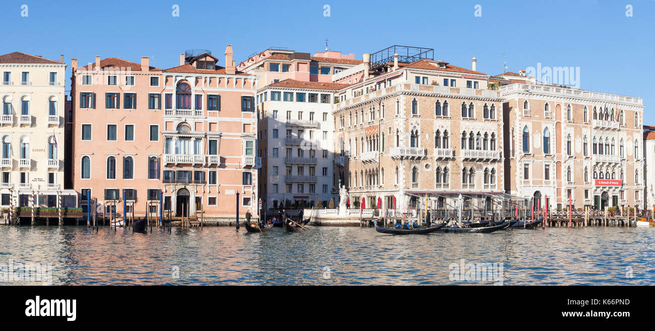Venice, Italy, Grand Canal panorama in winter sunshine with gondolas showing the Europa Hotel, Hotel Bauer palazzo and the Biennale di Venezia  in eve - Stock Image